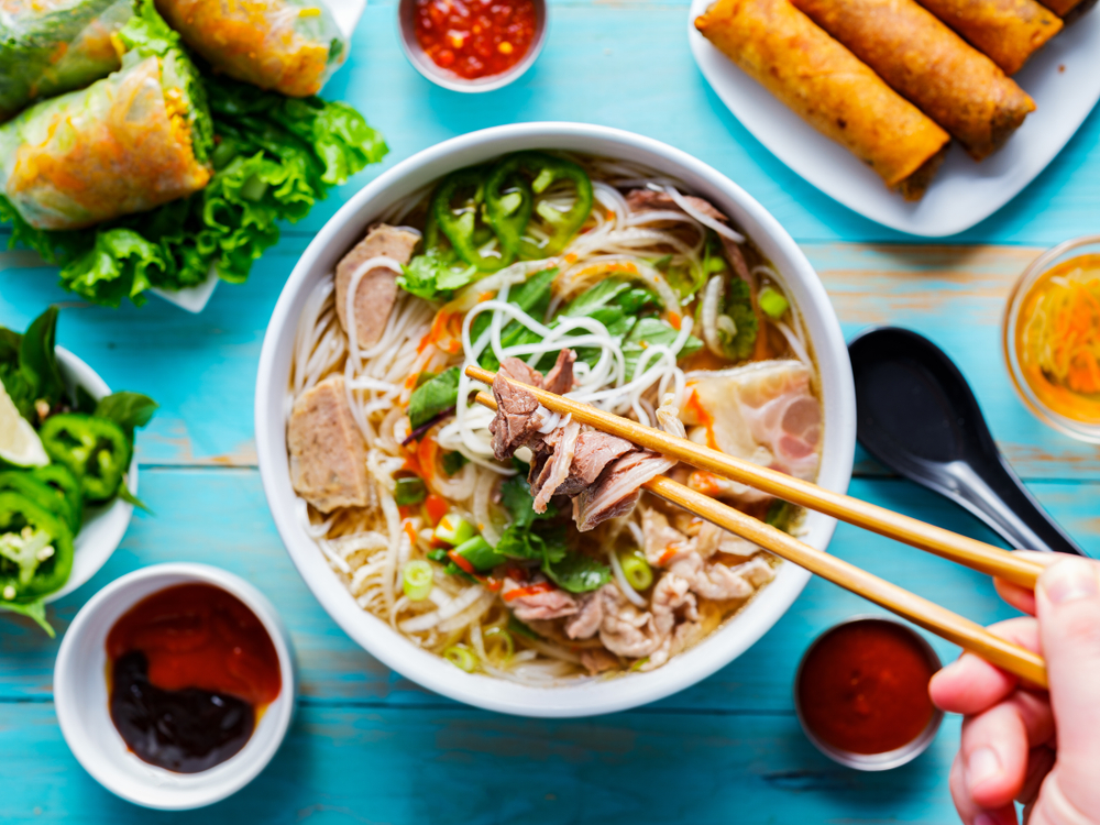 Bowl of pho surrounded by spring rolls and dips.