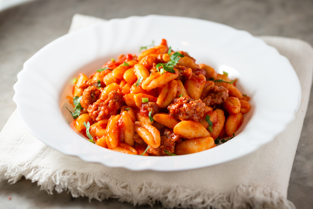 Pasta with red sauce served at one of the restaurants in Des Moines in a white bowl on a white linen napkin.