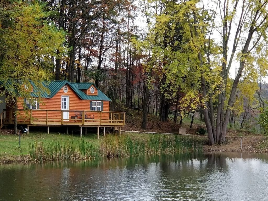Log cabin with green roof and wooden balcony/railing sits right next to tranquil lake VRBO in Ohio