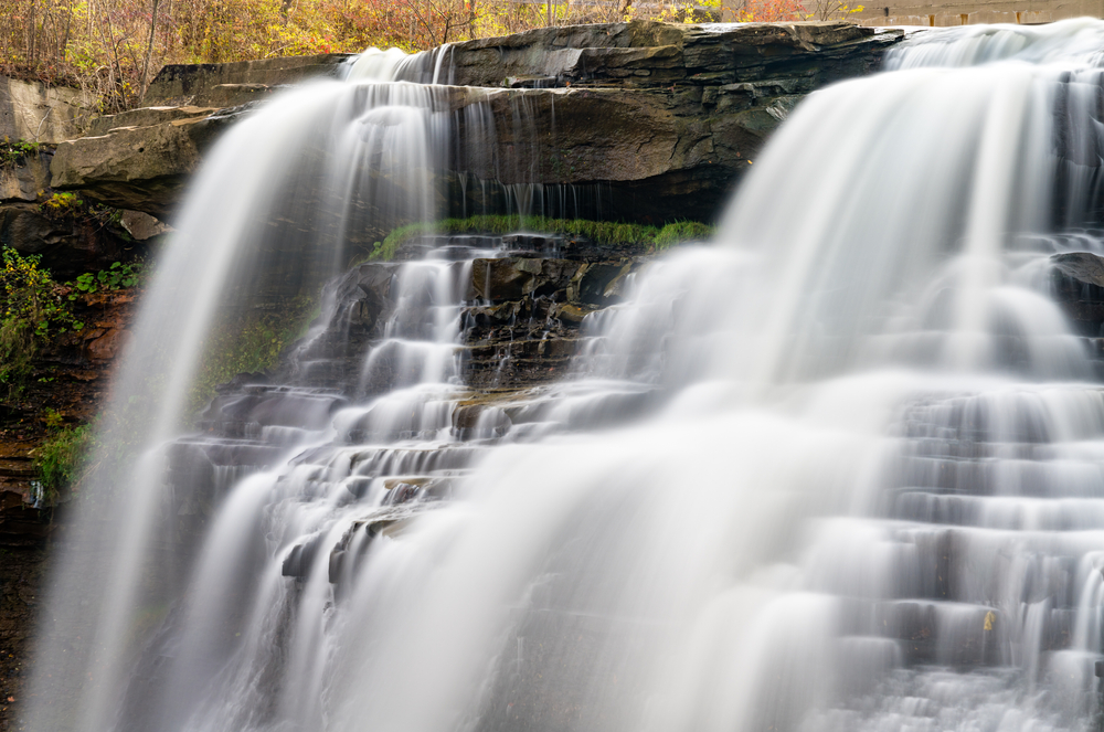 large cascading waterfall split in two, flowing down rock formations.
