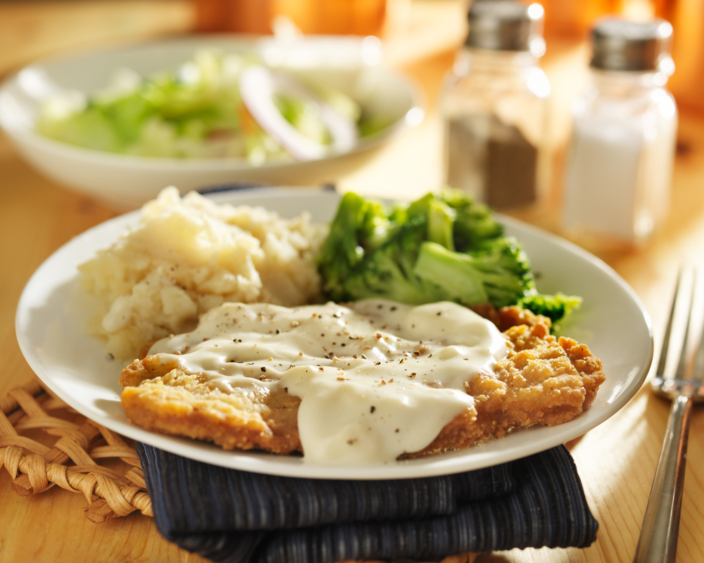 Chicken fried steak with mashed potatoes and broccoli.