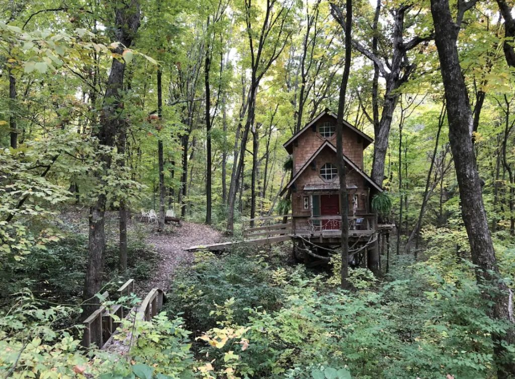 Rustic wooden cabin set deep in woods with long wooden bridge to get to front porch. Surrounded by dense forest.