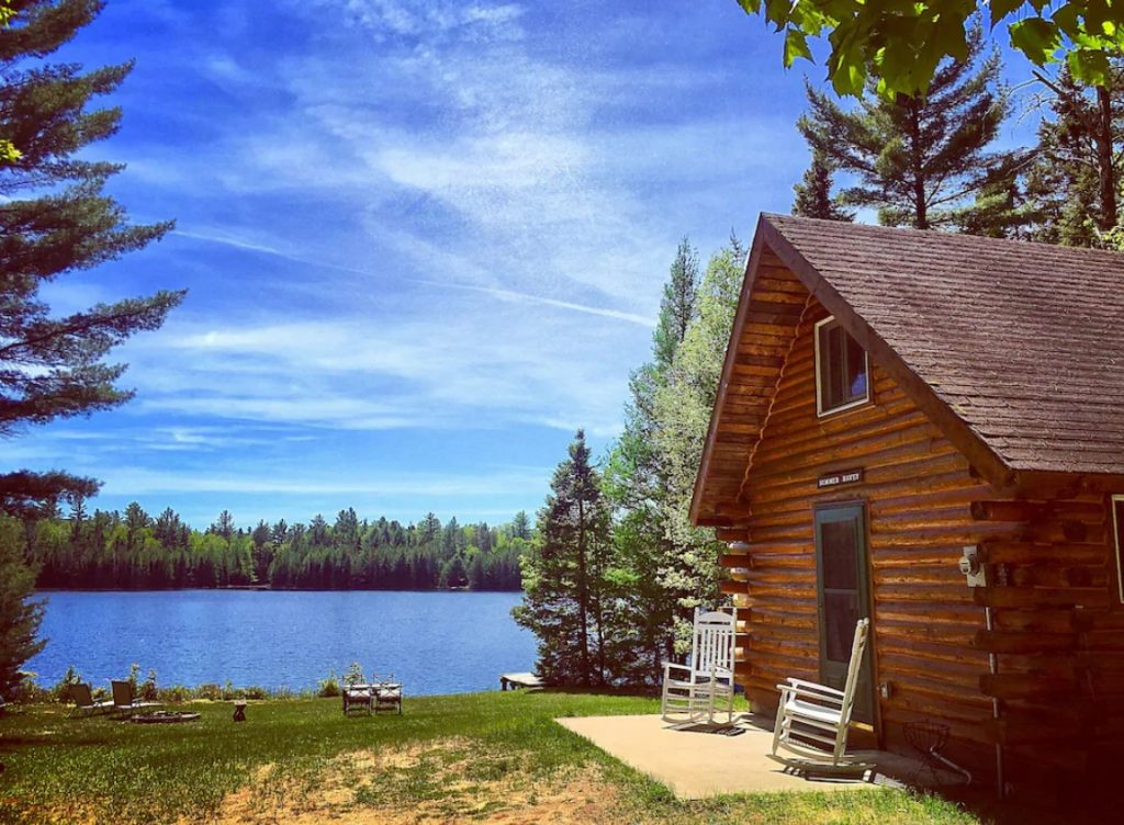 Log cabin with chairs on small patio with lake, dock and chairs near lake. Cabins in the Midwest.