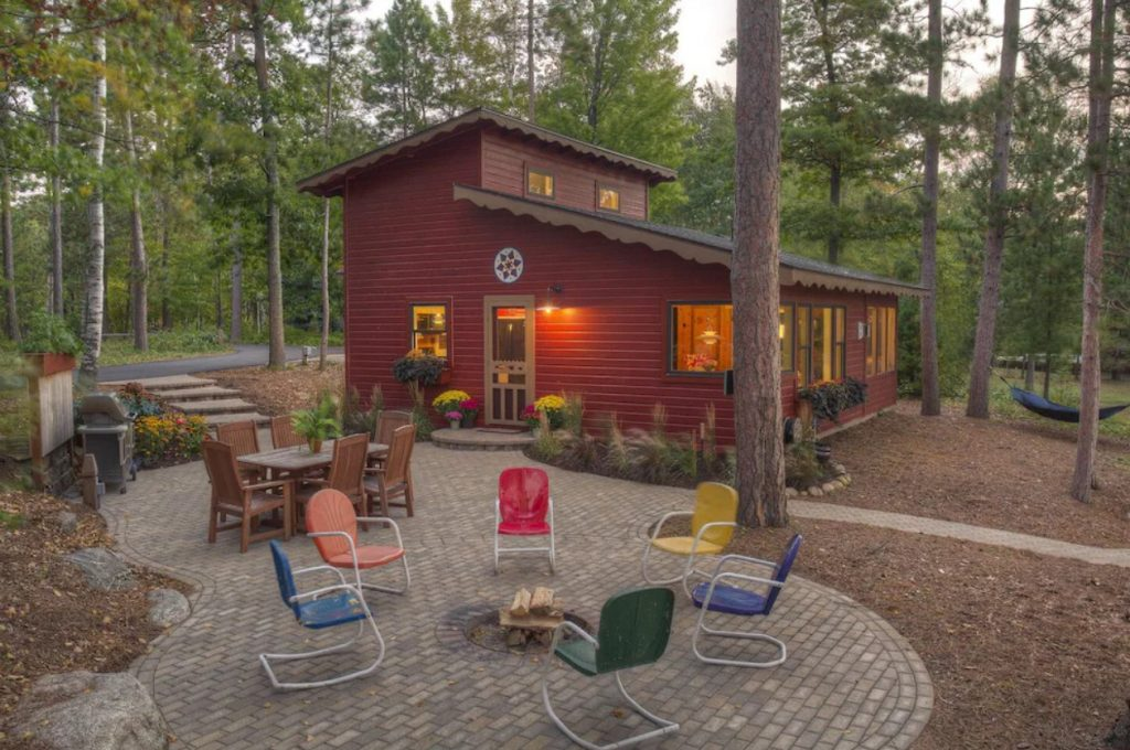 Brown log cabin with spacious yard in foreground. Stone paved fire pit area surrounded by colorful chairs. Table and chairs nearby.