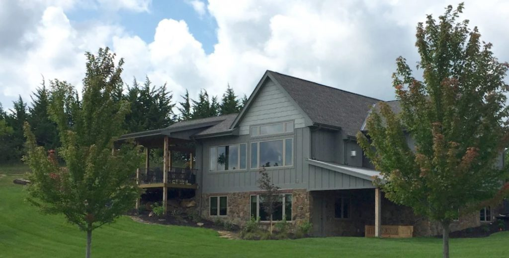 Stylish multi - level exterior of Midwest cabin with stone and gray siding. large balconies, manicured lawn in foreground.