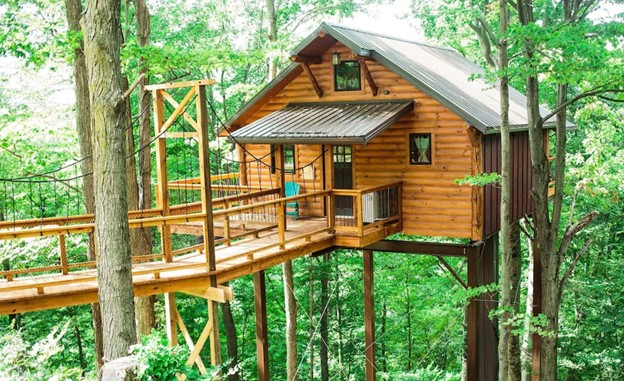 Log cabin treehouse up on wooded stilts and wooden walkway and balcony. Green metal roof. Cabins in the Midwest.
