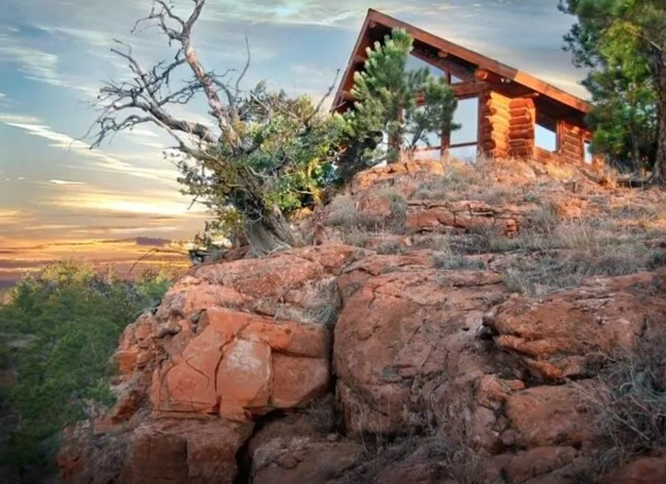 Cabin on tilltop with glass windows, sunset in background
