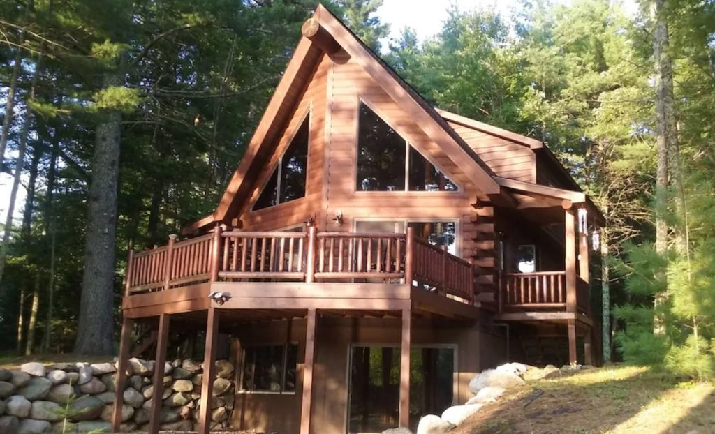 Luxury log cabin with A-frame roof, large wooden balcony, large glass windows, propped up by wooden beams .Green tees in background.