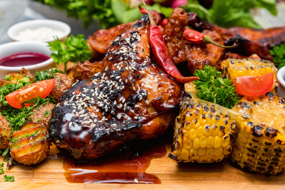 Barbecue Chicken and vegetables on a wooden plate in an article about restaurants in Branson