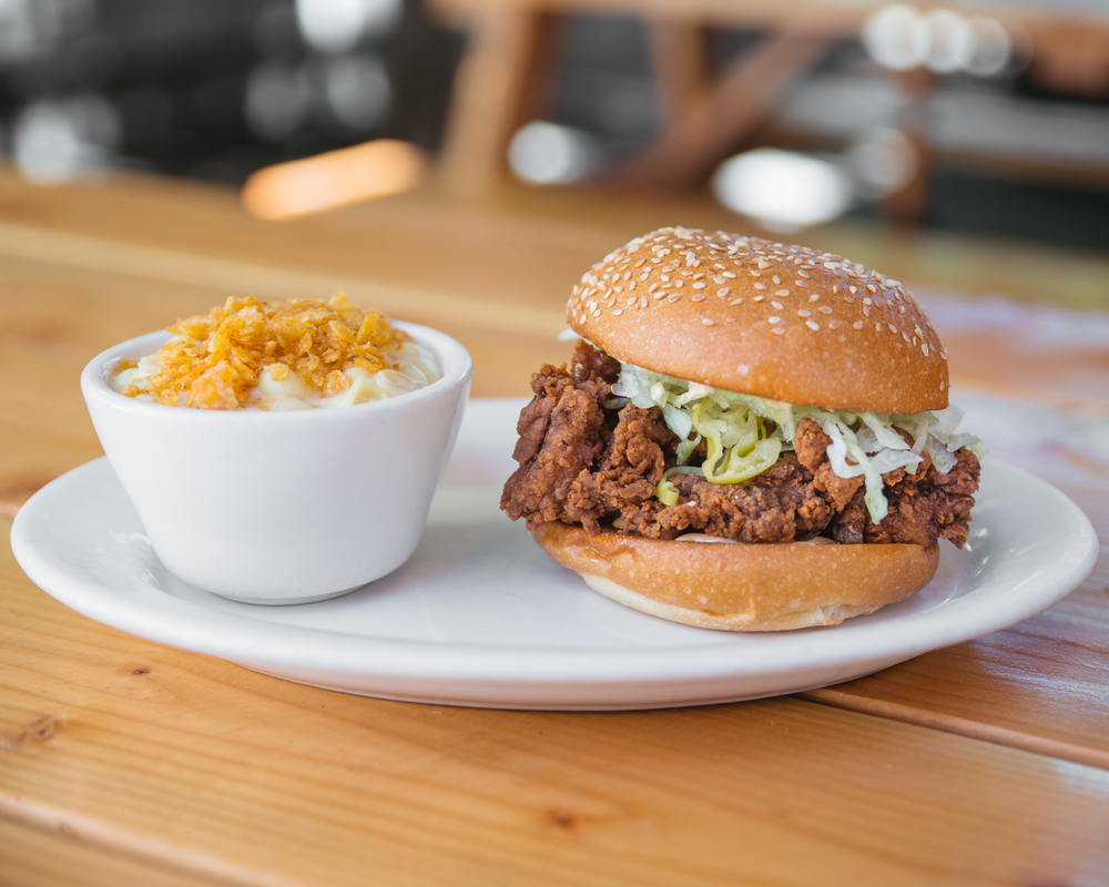A fried chicken burger in a bun on a white plate