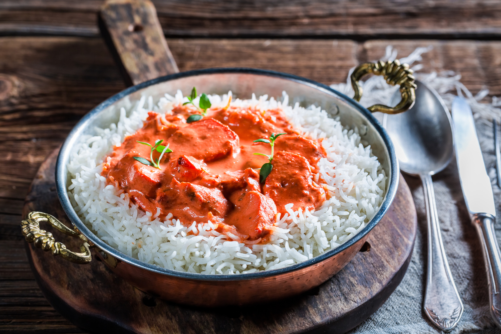 Tikka Masala with rice in a bowl on a wooden table