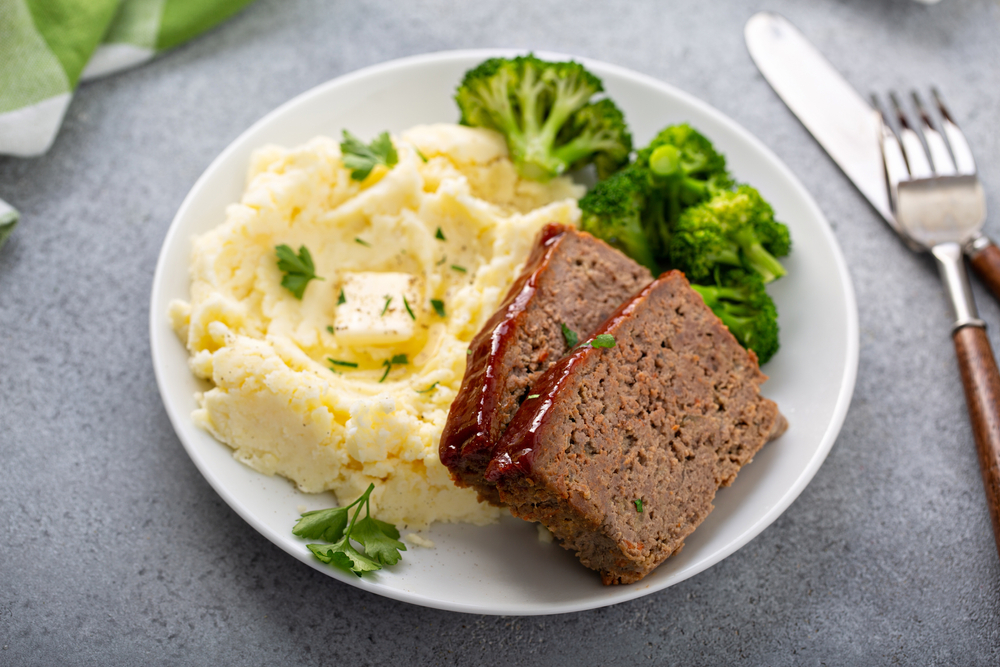 Meatloaf on a plate with broccoli and mashed potatoes