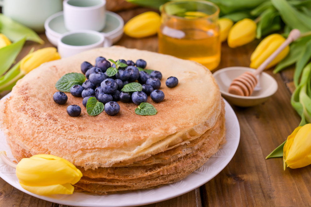 Large pancakes on a plate with blueberries on top and flowers around.