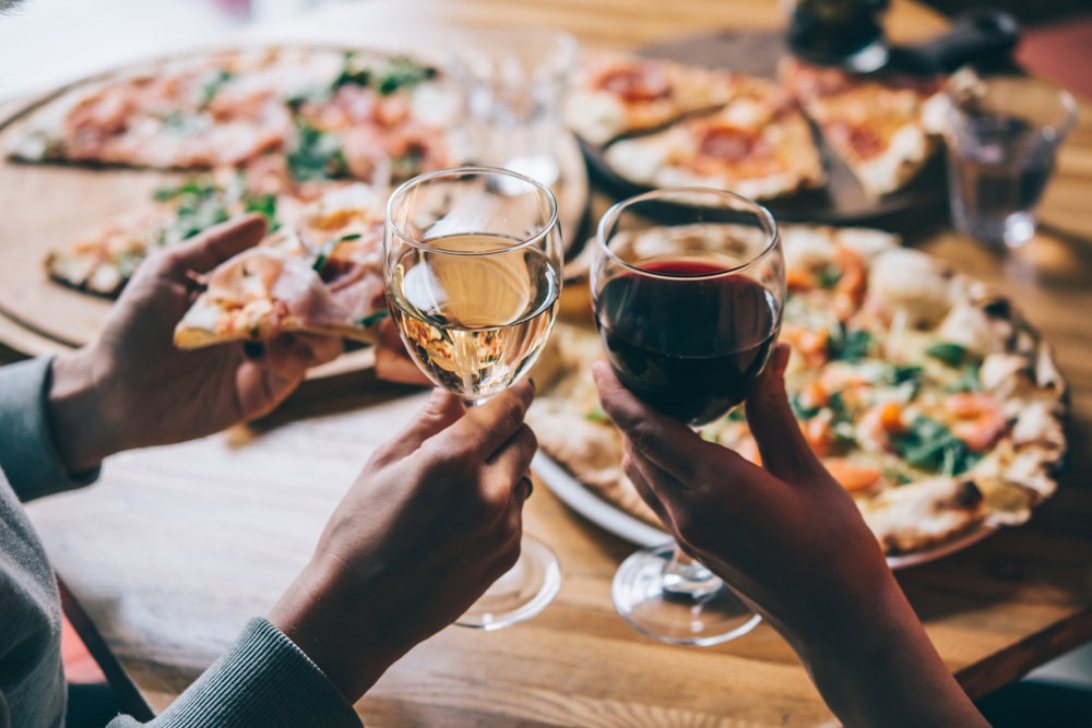 couple enjoying pizza on the table holding up two glasses of wine in an article about restaurants in Branson