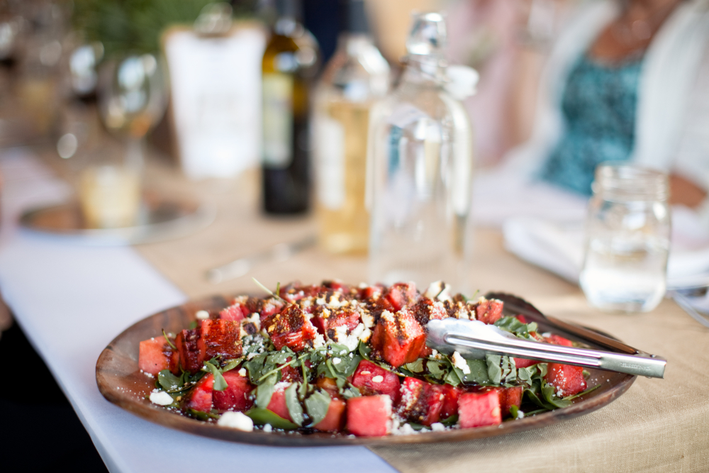 A beautiful looking fresh salad in a plate with wine in the background.