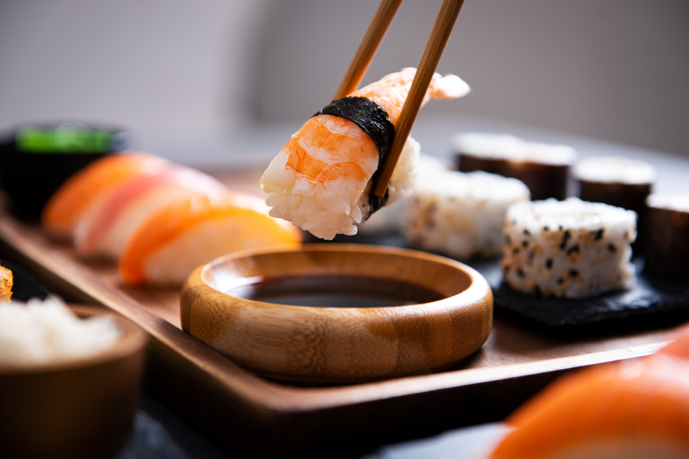 Close up of chopsticks picking up sushi on a wooden plate