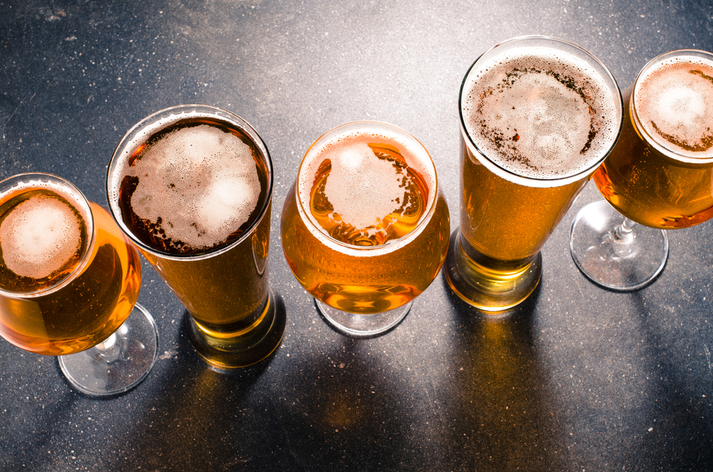 Beer in several types of glasses on dark table.