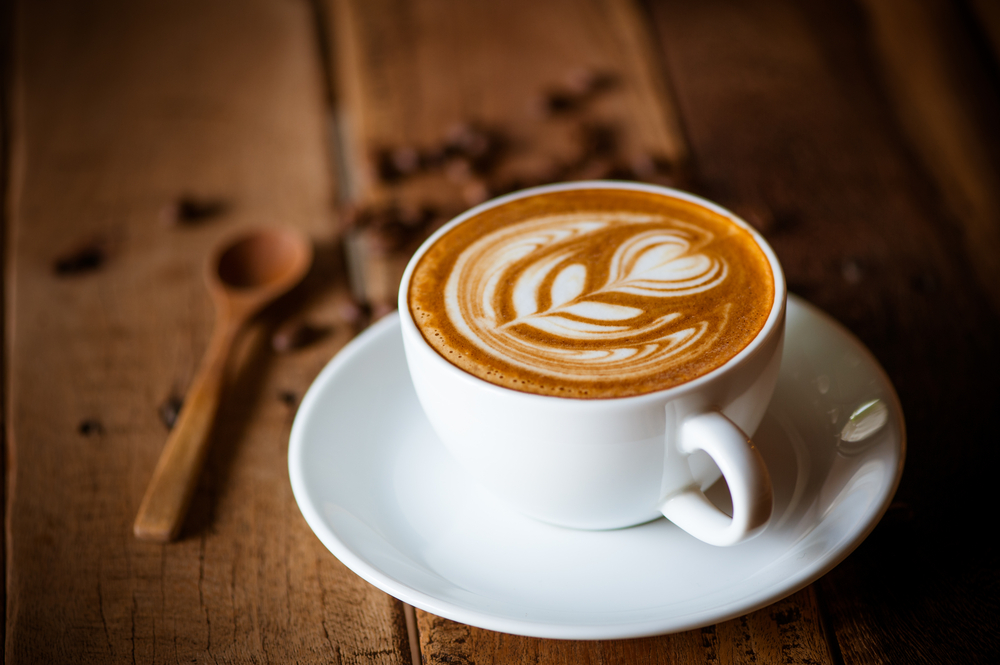 Cup of latte with cream flower decoration, on brown wooden table. Coffee beans and wooden spoon in background.