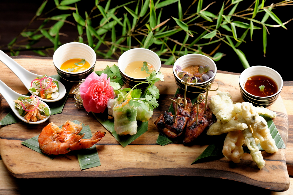 Asian Fusion food set on green leaves or in small cups all on wooden platter.