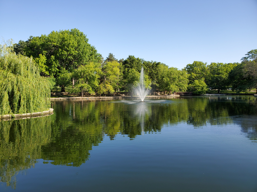 A lake at Loose Park with a fountain in the middle.