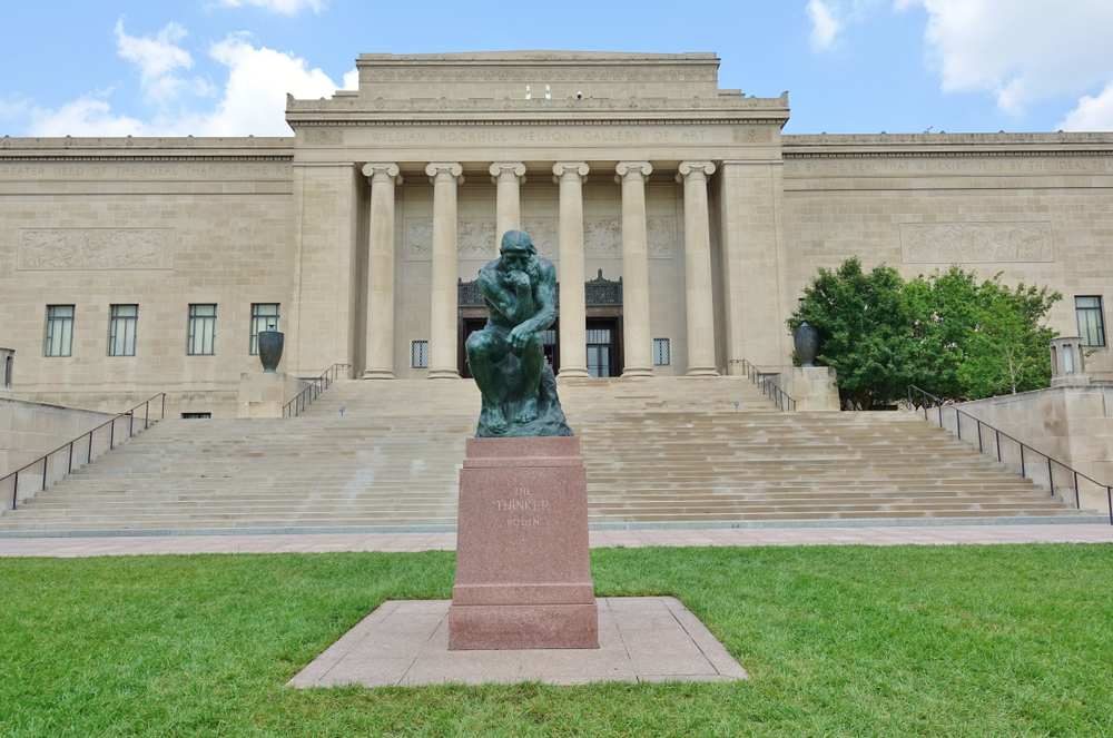 """View of the Nelson-Atkins Museum with a replica of Rodin's """"The Thinker"""" in front."""