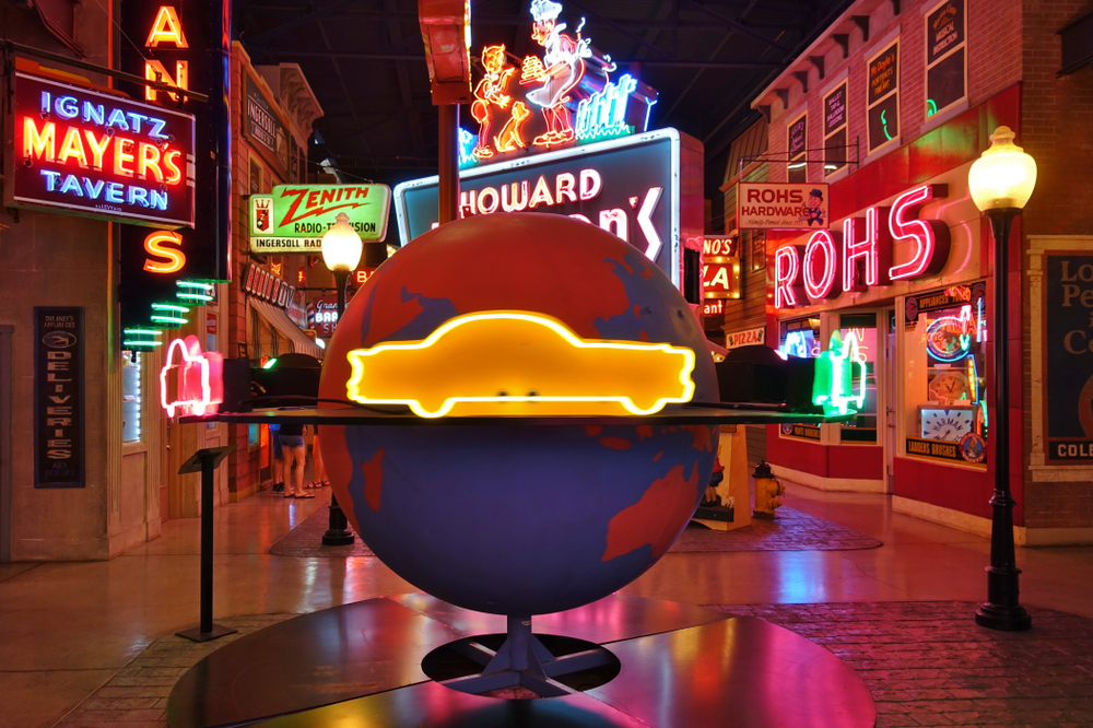 A bunch of neon signs on the side of store front facades in the American Sign Museum. They are all kinds of colors, shapes, and say different things. In the middle is a large globe  with a neon yellow car going around it.