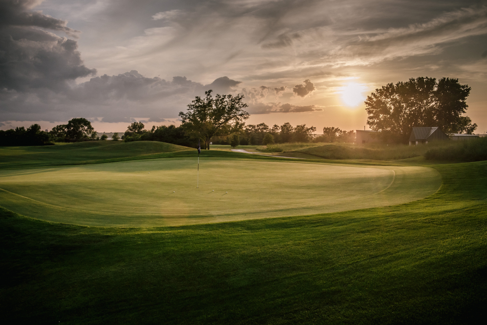 A large golf course at sunrise in Nebraska. There is some fog in the air and clouds are making the sun not so bright. The golf course is very green.