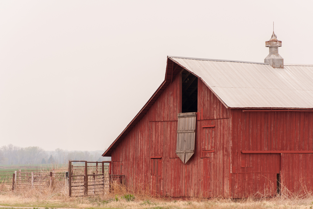 An old red barn on a prairie in Nebraska. There is fog in the air and the sky is very gray. One of the best things to do in Lincoln.