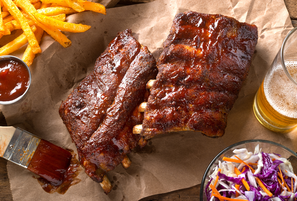 A rack of bbq ribs on a piece of butcher paper at one of the bbq restaurants in Omaha. You can also see a brush with bbq sauce on it, a small dip bowl with ketchup, fries, coleslaw, and a glass with some beer in it.