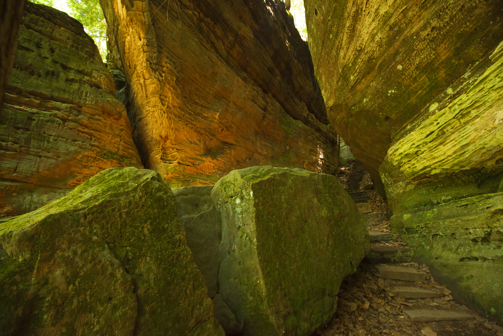 Huge moss-covered boulders on top of one another with stone steps right through middle.