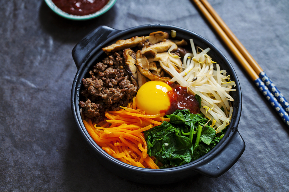 A black bowl on a black table that has a set of chopsticks next to it. In the bowl there is grilled mushrooms, grated carrot, ground beef, bean sprouts, wilted spinach, and a soft egg yolk.