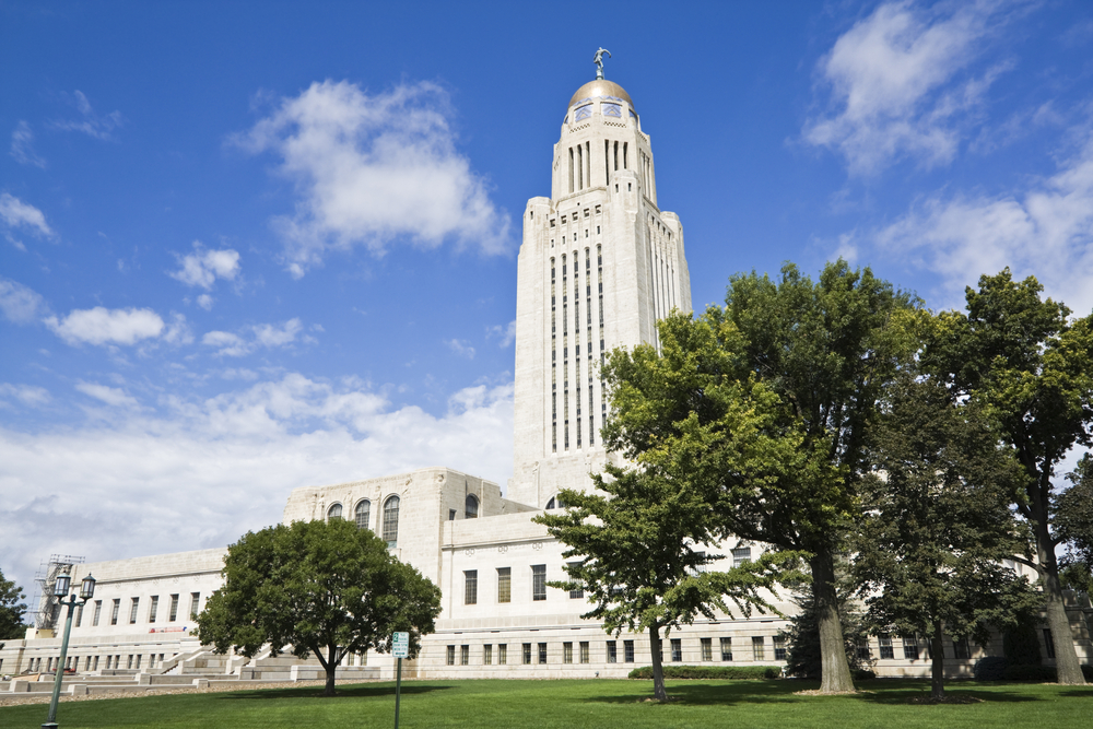 The exterior of the large white Nebraska State Capitol Building. It is long with lots of windows and in the center is a very tall tower with a silver dome and a sculpture on top of it.