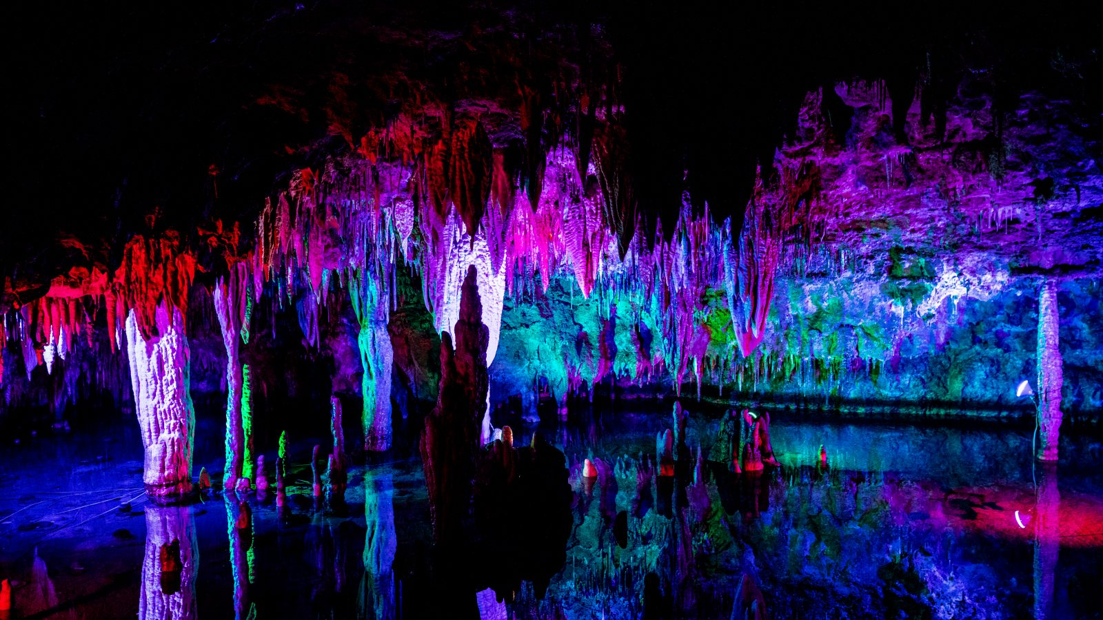 Meramec Caverns lit up with colored lights showing stalactites and water