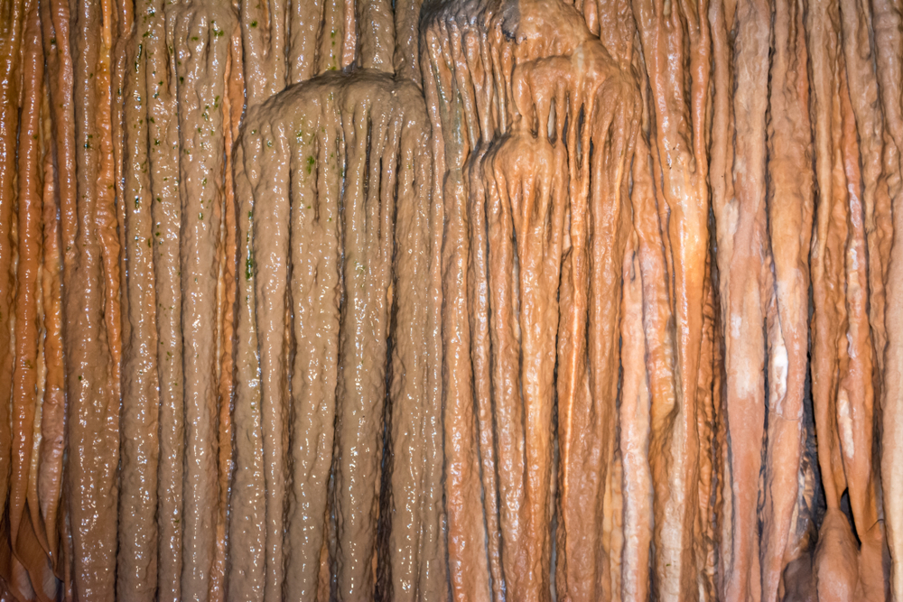 A curtain cave formation in a cave in Missouri displaying brownish vertical rock formations.