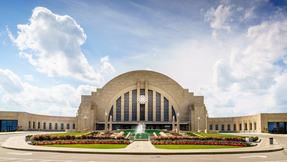 The exterior of the Cincinnati History Museum in the old Union Terminal Station. There are flowers in front of it that are red, white, yellow, and there is a green lawn with a water fountain.