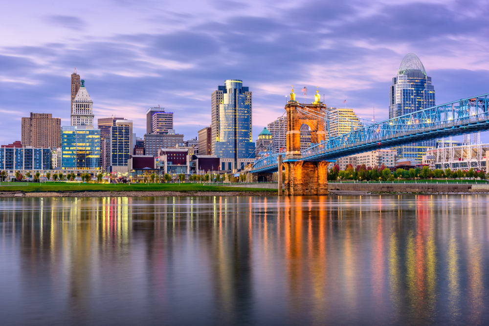 The Cincinnati skyline at twilight across the Ohio River. The buildings are lit up, the sky is purple and pink, and you can see the lights of the buildings in the river.