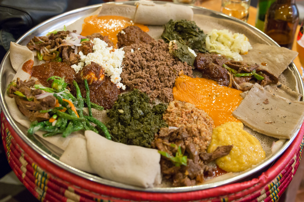 A large platter with a variety of Ethiopian foods like you can find at the Ethiopian restaurants in Lincoln. There is ground meat, cooked greens, sauces, and a type of flatbread.