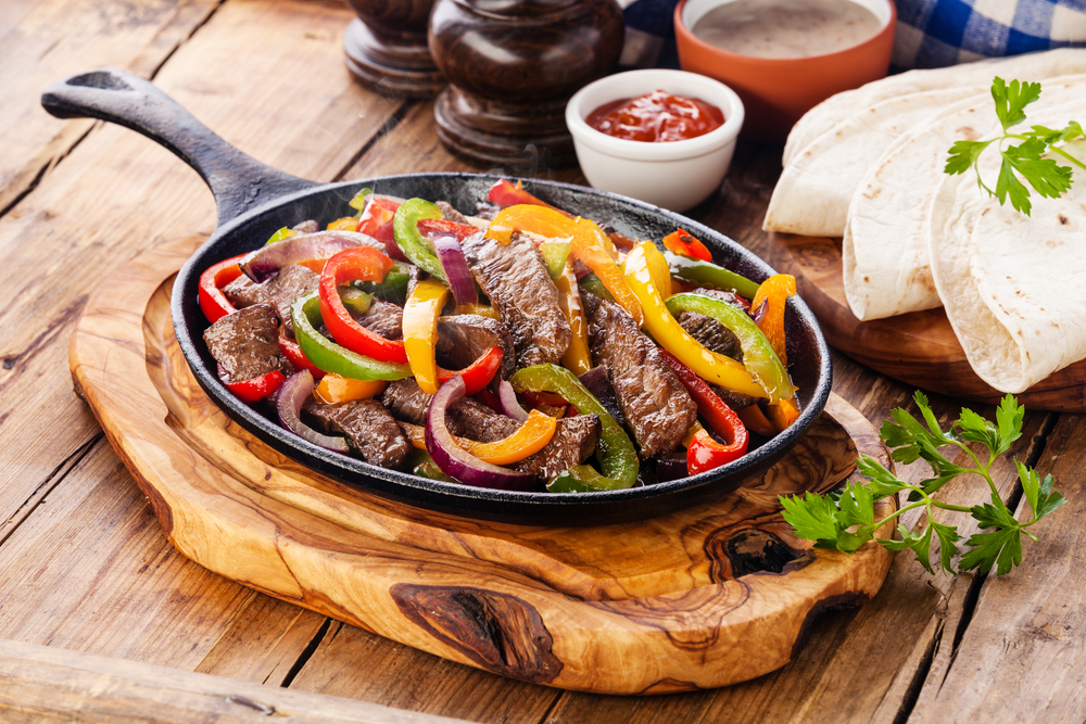 A skillet full of sliced beef, peppers, and onions to make fajita filling. The skillet is on a piece of wood on a wooden table and you can see a bowl of salsa, flour tortillas, and sprigs of cilantro.
