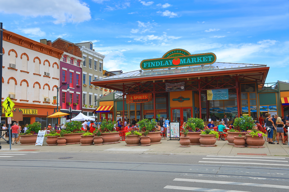 The exterior of Findlay Market, one of the best things to do in Cincinnati. There are large terracotta pots with plants in them at the front. There are people standing around outside.