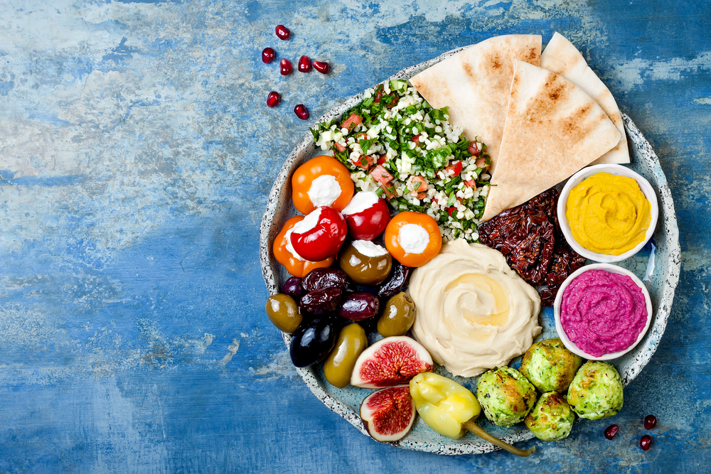 Looking down at a large platter of Greek food on a blue white-washed table top. The platter has hummus, roasted brussels sprouts, stuffed tomatoes, olives, pita bread, and a couscous salad. Its similar to what you can find at one of the best Greek restaurants in Lincoln Nebraska.