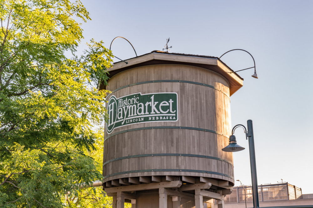 The wooden water tower in the heart of the Historic Haymarket District, one of the best things to do in Lincoln. Next to it is a large tree and a tall light post.