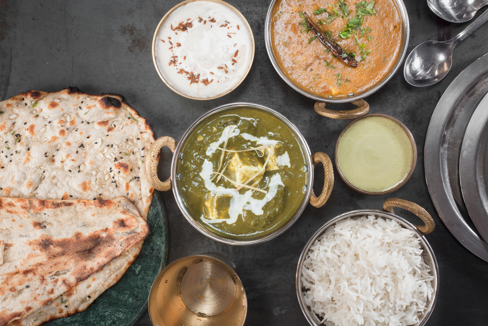 Looking down at a black table covered in dishes full of traditional Indian cuisine. There is paneer in a green sauce, an orange curry, a white yogurt sauce, a green yogurt sauce, biryani rice, and naan bread.