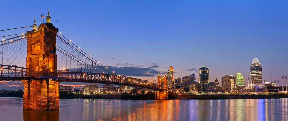 A view of the John A. Roebling Suspension Bridge, one of the coolest things to do in Cincinnati. It is twilight and the bridge is lit up. You can also see a city lit up on the other side of the bridge.