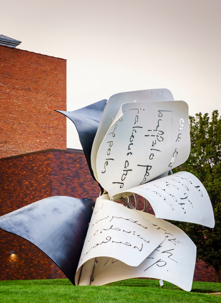 A large outdoor sculpture that looks like book pages flapping in the wind. It is made of metal and has words carved into it. It is outside the Sheldon Art Museum, one of the best things to do in Lincoln.