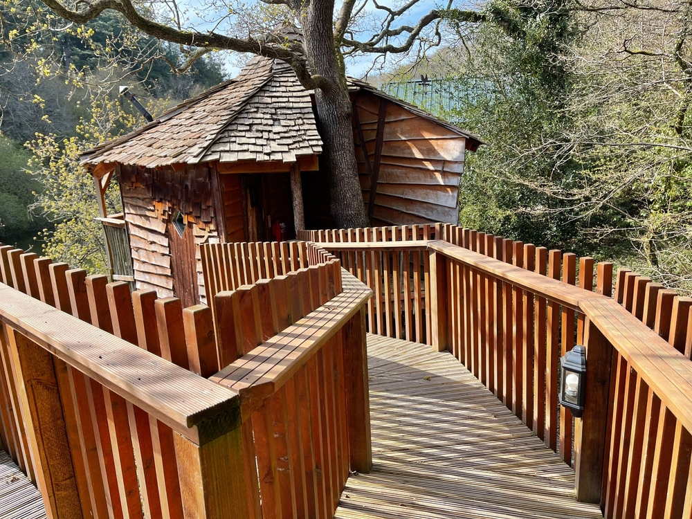 A treehouse like the one in the Mt. Airy Forest, one of the best things to do in Cincinnati Ohio. There is a wooden walkway, a small treehouse with wooden shingles, and it is surrounded by trees.