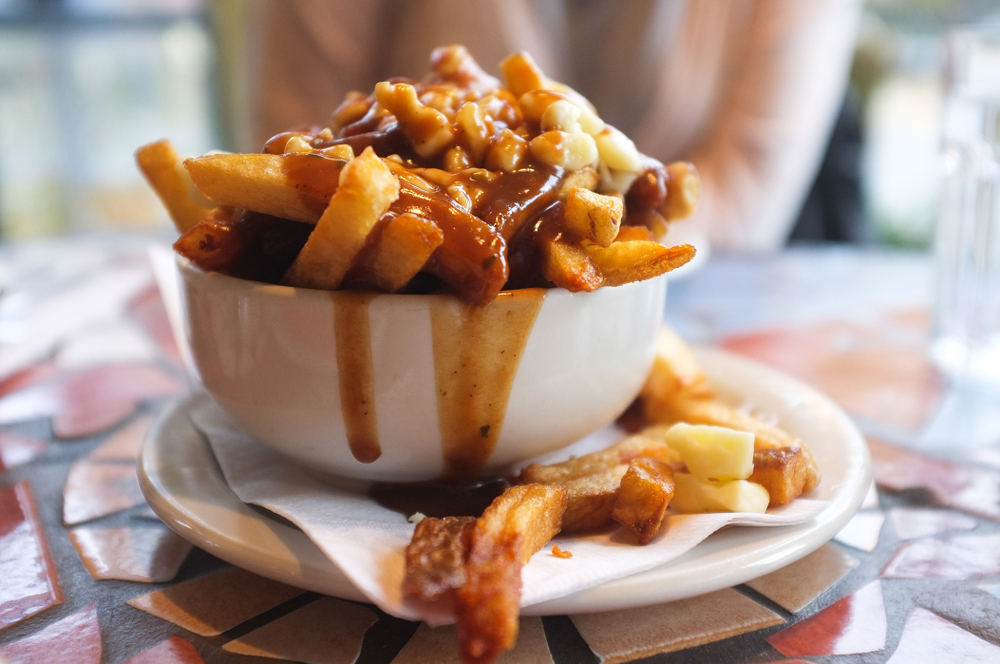 A white bowl on a saucer on a mosaic table. The bowl is overflowing with French fries covered in poutine.