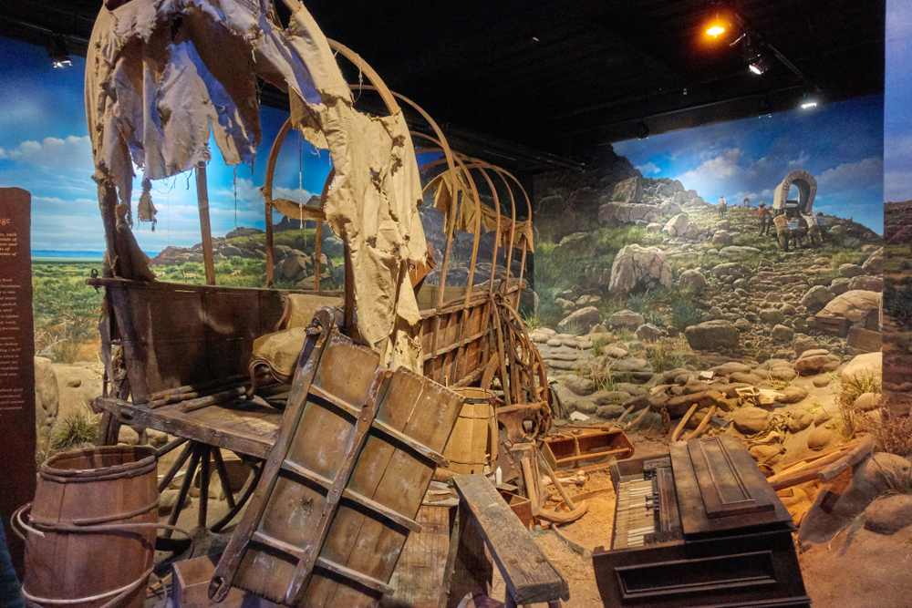 A display of a pioneer wagon that is torn apart in a museum in Lincoln NE. Behind it there is a painting of pioneers making their way west.