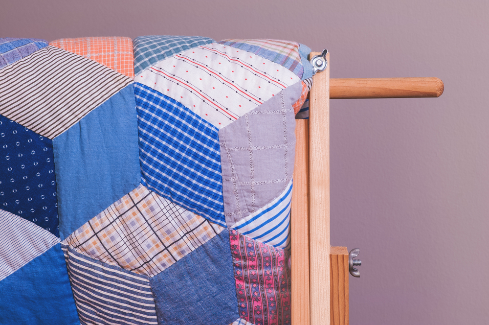 A quilt on display that has fabric with all kinds of patterns in shades of blue, purple, pink, orange, and red. The pieces are cut into trapezoids.