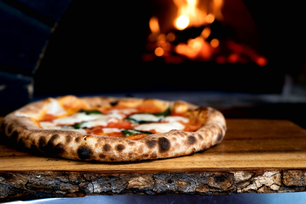 Wood-fired pizza with browned crust on wooden paddle. Fire in background. Restaurants in Columbus.