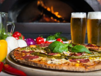 wood-fired pizza with frest veggies and two glasses of beer.